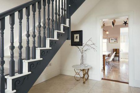 Hallway stairs,marble flooring,side table,artwork