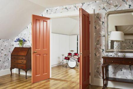 Loft room with storage,doorway,timber flooring,slanted ceiling,wallpaper